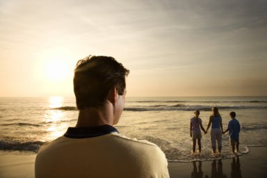 Man watching family on beach